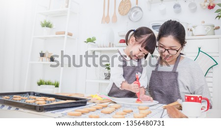 Portrait of little asian girl and mother baking cooking decorate cake and cookies in the kitchen. Happy asian family love together parenthood food nutrition Asia mother's day concept banner