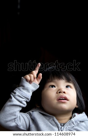 Portrait of little baby girl in curiosity isolated in dark background