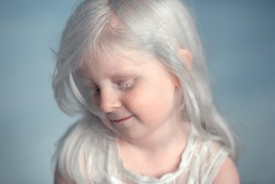 Portrait of little beautiful albino girl. Image with selective focus and toning