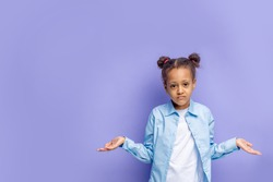 portrait of little beautiful girl standing isolated over purple background, embarassed facial expression with hands up. Doubt concept