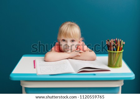 Portrait of little blonde girl is sitting at the table and paints. Schoolkid is doing her homework in classroom at school or at home. Tired and sad pupil