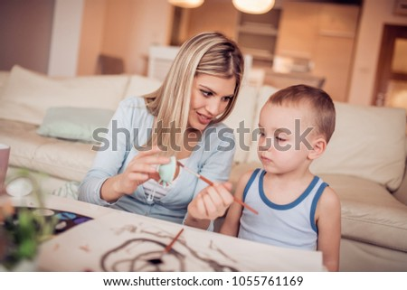 Portrait of little boy and mother coloring eggs for Easter.Easter,family,love and happiness concept. #1055761169