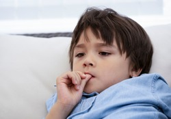 Portrait of little boy biting his finger nails while watching TV,Head shot kid with deep in thought, Childhood and family concept, Emotional Child portrait.