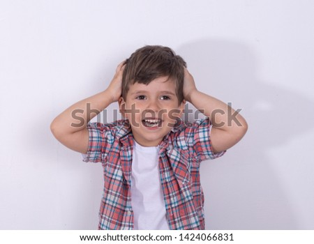 Portrait of little boy holding hands on head, screaming. Close up of funny boy being shocked or amazed. Child's big eyes widened.