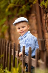 portrait of little boy in the blue shirt and  cap is standing near the wooden fence in the park