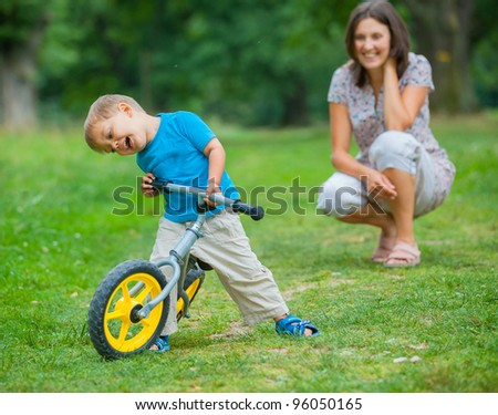 Portrait of little boy on a bicycle and his mother in the summer park