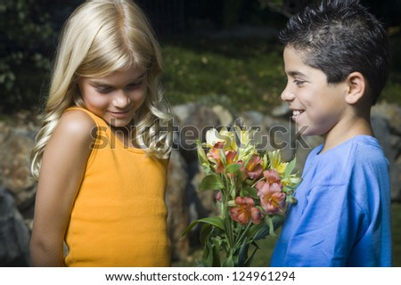 Portrait of little boy presenting flowers to girl