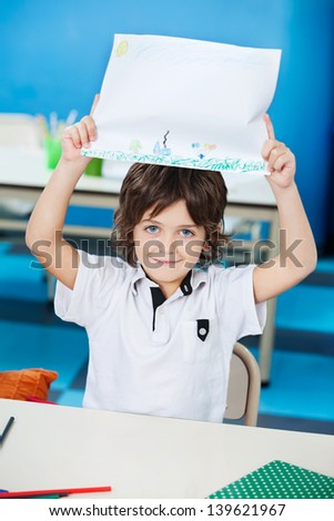 Portrait of little boy showing drawing paper in classroom