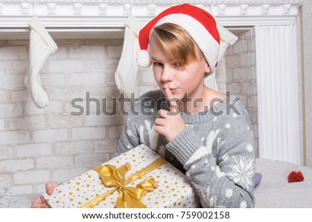 Portrait of little boy. Smiling funny child in Santa red. Christmas concept.  Teen with gifts at the fireplace and christmas tree. Merry Christmas and Happy Holidays.  Close up portrait.