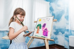 Portrait of little caucasian girl painting with copy space watercolor in her art kindergarten classroom. Young creative gifted artist home school education learning by doing back to school concept