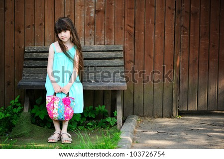 Portrait of little child girl sitting on a bench in a park