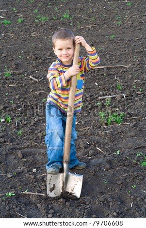 Portrait of little children digging a big shovel in the field