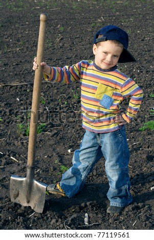 Portrait of little children with big shovel in the field