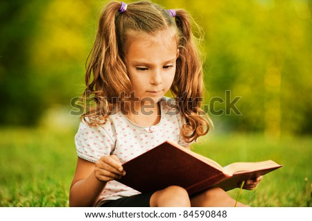 Portrait of little cute fair-haired girl reading book, sitting at summer green park.