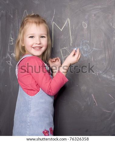 portrait of little cute girl near blackboard - stock photo