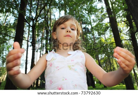 Portrait of little cute girl with curly blonde hair in white clothes inside green forest, she throws up hands, focus on face