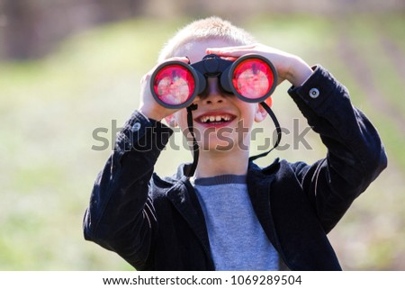 Portrait of little cute handsome cute blond boy watching intently something through binoculars in distance on blurred background. Children innocence, dreams, fantasies and imaginations concept. #1069289504