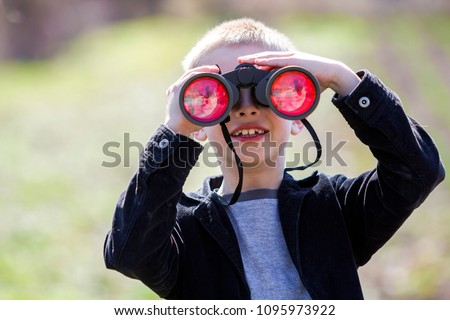 Portrait of little cute handsome cute blond boy watching intently something through binoculars in distance on blurred background. Children innocence, dreams, fantasies and imaginations concept. #1095973922