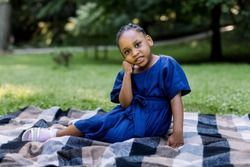 Portrait of little cute happy African girl in blue dress, sitting on checkered blanket in summer park, having a picnic time. Happu childhood, summer portrait, copy space