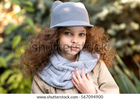 Portrait of little cute smiling girl in funny cat hat with long curly hair. Outdoor in the garden.