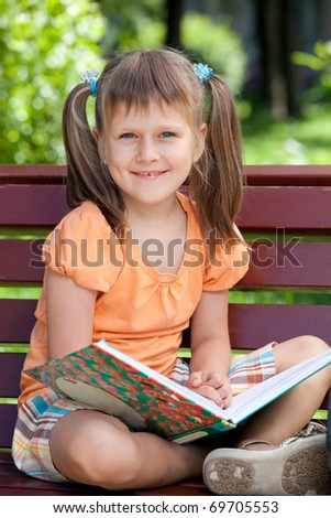 Portrait of little cute smiling girl preschooler with open book who is sitting cross-legged on the wooden bench in summer park