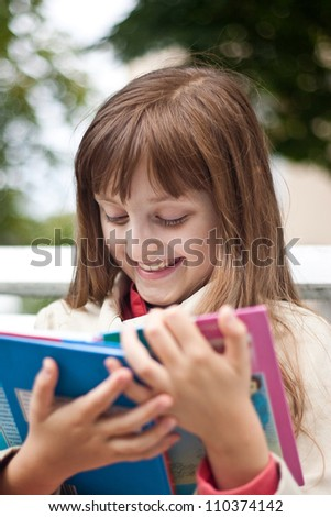 Portrait of little cute smiling girl schooler with open book is sitting  on the wooden bench in summer park