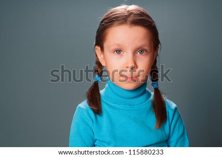 Portrait of little girl against grey background,