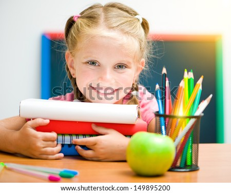 Portrait of little girl at workplace with the books