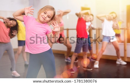 Portrait of little girl doing exercises during group class in dance center Photo stock ©