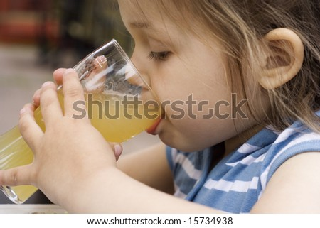 portrait of little girl driking an apple juice