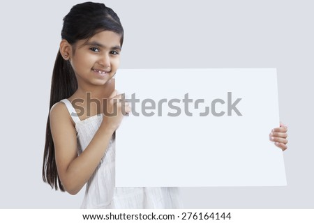 Portrait of little girl holding a white board