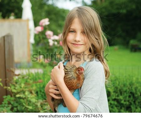 Portrait of little girl holding chicken in hands