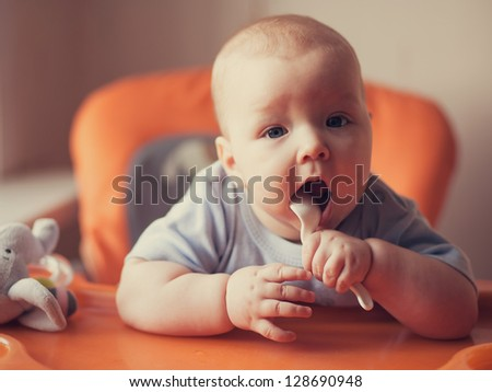 Portrait of little girl holding spoon #128690948