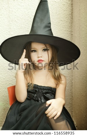Portrait of little girl in black hat and black clothing