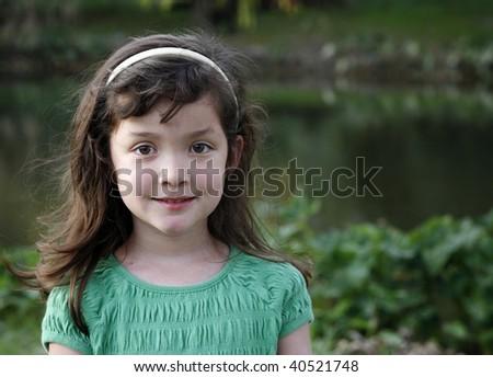 Portrait of little girl in green environment