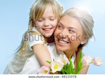 Portrait of little girl loving mother holding her and tulips