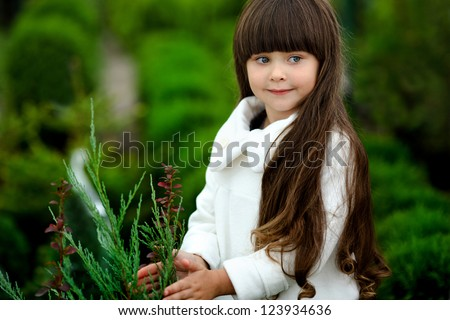 portrait of little girl outdoors in the style of gardener