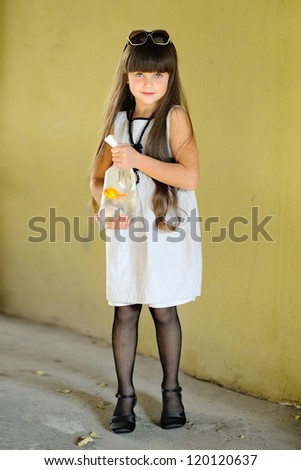 portrait of little girl outdoors with a goldfish