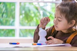 Portrait of little girl painting a ceramic model at school. Concept for art and creative education. Kids concept hobby.