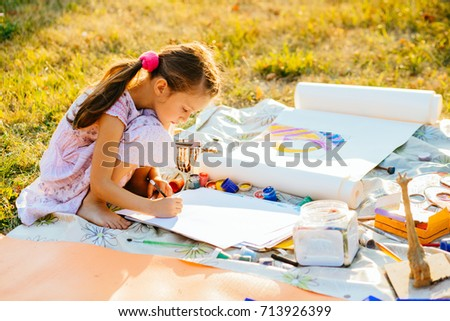 Portrait of little girl painting, summer outdoor. Art, drawing and kids creativity concept.