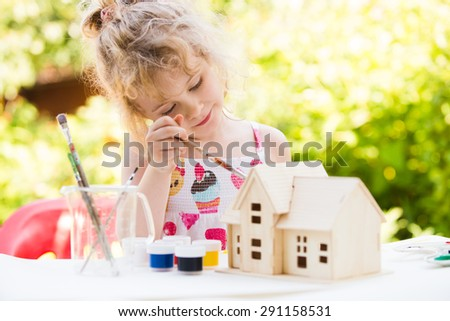 Portrait of little girl paints wooden model of house,  summer outdoor, new home concept