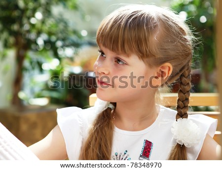 portrait of little girl sitting alone outdoors - stock photo