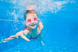 Portrait of little girl swimming underwater in pool