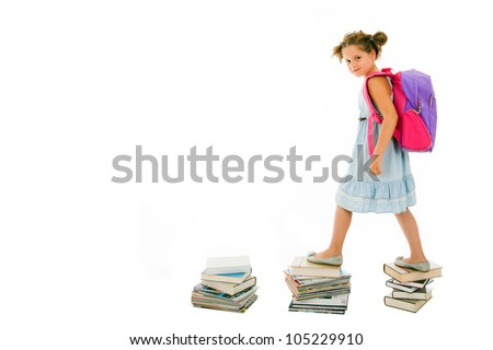 Portrait of little girl with backpack walking from top to top of book piles