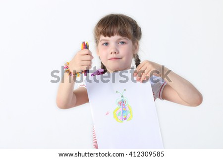 Portrait of little girl with crayons shownig her picture in white studio