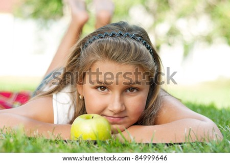 Portrait of little girl with green apple outdoor