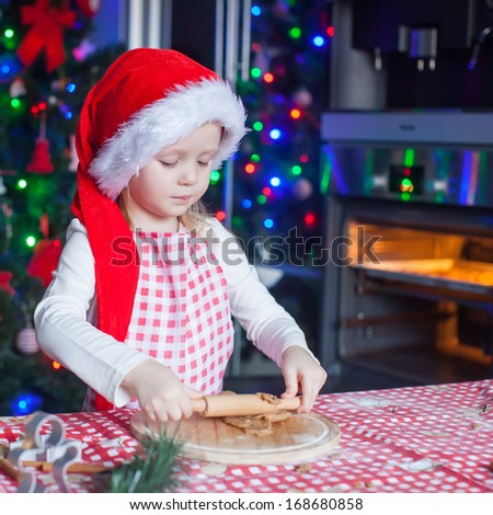 Portrait of little girl with rolling pin baking Christmas gingerbread cookies