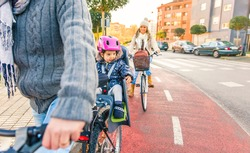 Portrait of little girl with security helmet on the head sitting in bike seat and her mother with bicycle on the background. Safe and child protection concept.