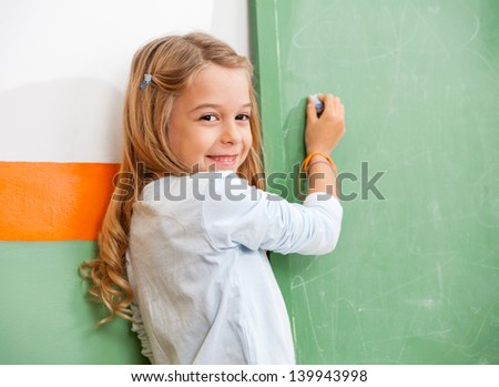 Portrait of little girl writing on green chalkboard in classroom