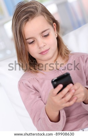 Portrait of little girl writing short message on mobile phone